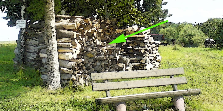 Bank mit Holzstapel dahinter, auf den ein Pfeil zeigt