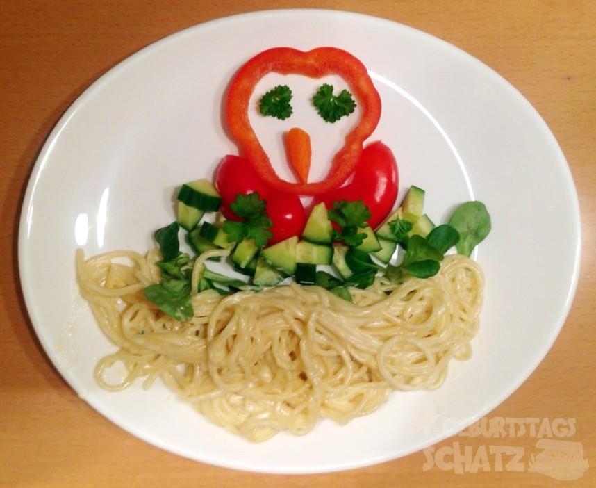 Vogel aus Paprika in einem Nest aus Spaghetti und Feldsalat-Salatgurken-Mix.