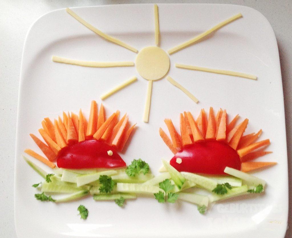 zwei Igel aus Paprika mit Karottenstacheln auf Salatgurkengras unter einer Käsesonne.