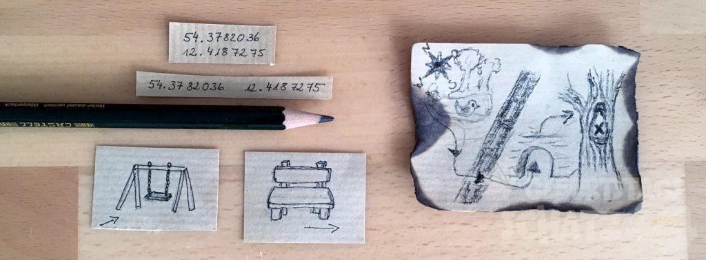 Kleine Zettel mit Strichzeichnungen oder GPS-Koordinaten für eine Schatzsuche, zwischen ihnen ein Bleistift, rechts daneben eine angekokelte Miniatur-Schatzkarte.