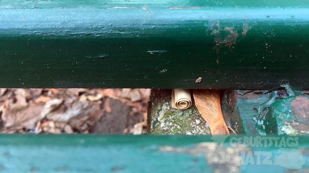 Bildausschnitt: Eine Mini-Papierrolle ist unter der Rückenlehne einer Parkbank versteckt.