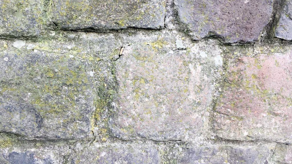 Eine Steinmauer, in einer Ritze ist ein Zettel versteckt.