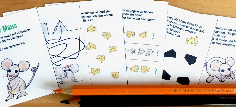 Die kleinen Rätselzettel der Miniaturschatzsuche liegen gefächert auf einem Holztisch. Darunter zwei Buntstifte, orange und schwarz. Die Rätsel enthalten kurze Texte, sowie Maus- und Käsebilder.