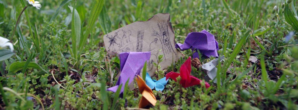 Mini-Origamis stehen im Gras und gucken auf eine kleine Schatzkarte. Ein lila Delfin, blauer Schmetterling, roter Kolibri, lila Elefant und grauer Hase.