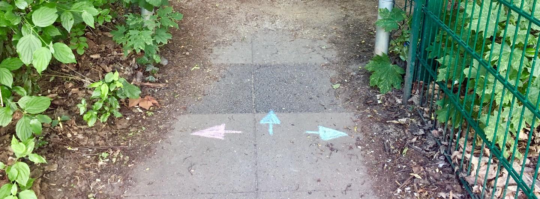 Auf einem gepflasterten Weg sind drei Pfeile mit Straßenmalkreide aufgemalt. Ein roter nach links, ein blauer geradeaus und ein grüner nach rechts.