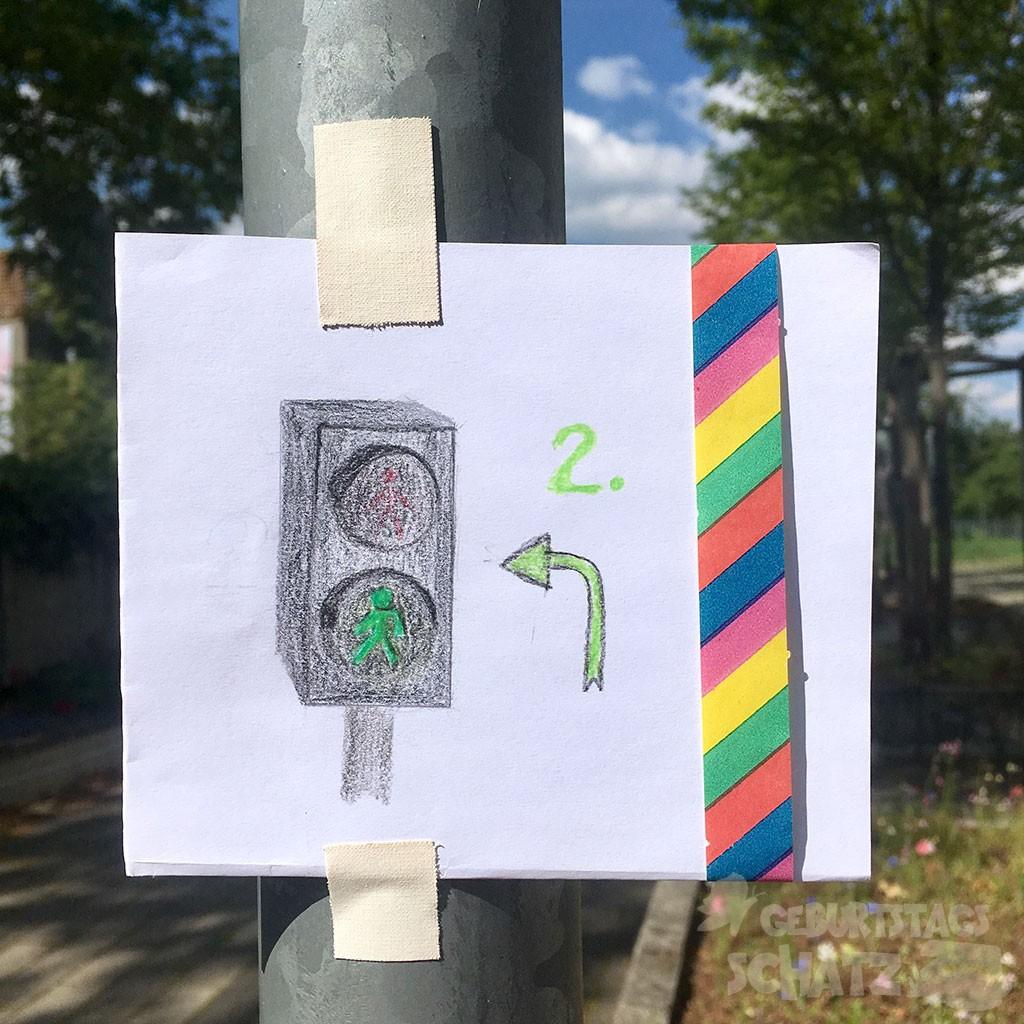 Ein Zettel mit aufgemalter Fußgänger-Ampel, daneben eine und ein nach links abbiegender Pfeil darunter. Ganz rechts ein Streifen einer bunten Luftschlange.