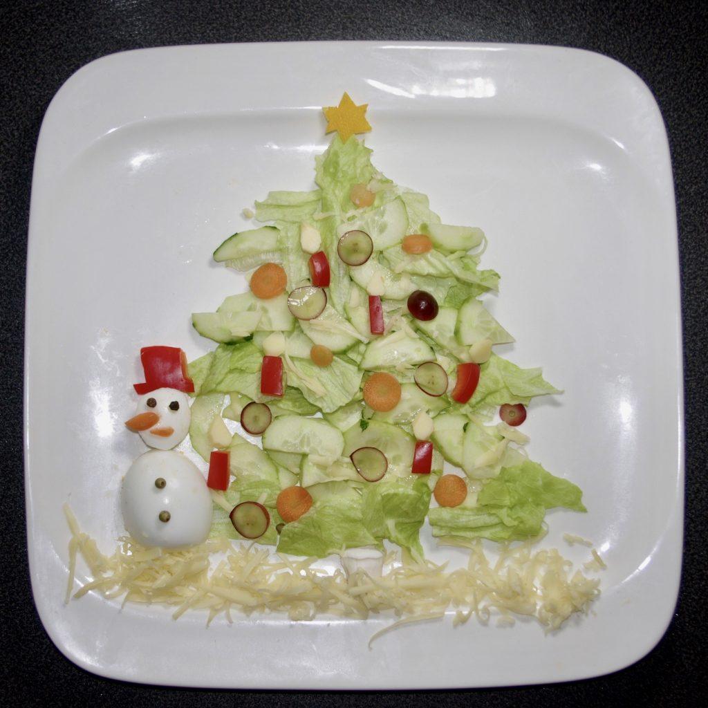 Ein Teller mit einem Salat, der als Bild gelegt ist. Ein Tannenbaum in der Mitte ist aus Salatgurken und Eisbergsalat gemacht, mit einem Stamm vom Champignon. Ein Schneemann links daneben ist ein gekochtes Ei, mit Pfefferaugen und- knöpfen. Die Nase ist stilecht aus einer Karotte gemacht. Sein Hut ist genau wie die Kerzen aus roter Paprika, deren Flammen aus Gouda geschnitzt sind. Die Tannenbaumkugeln sind aus Karotten- und Weintraubenscheiben geschnitten. Das ganze steht auf einem Bett aus geraspeltem Gouda.