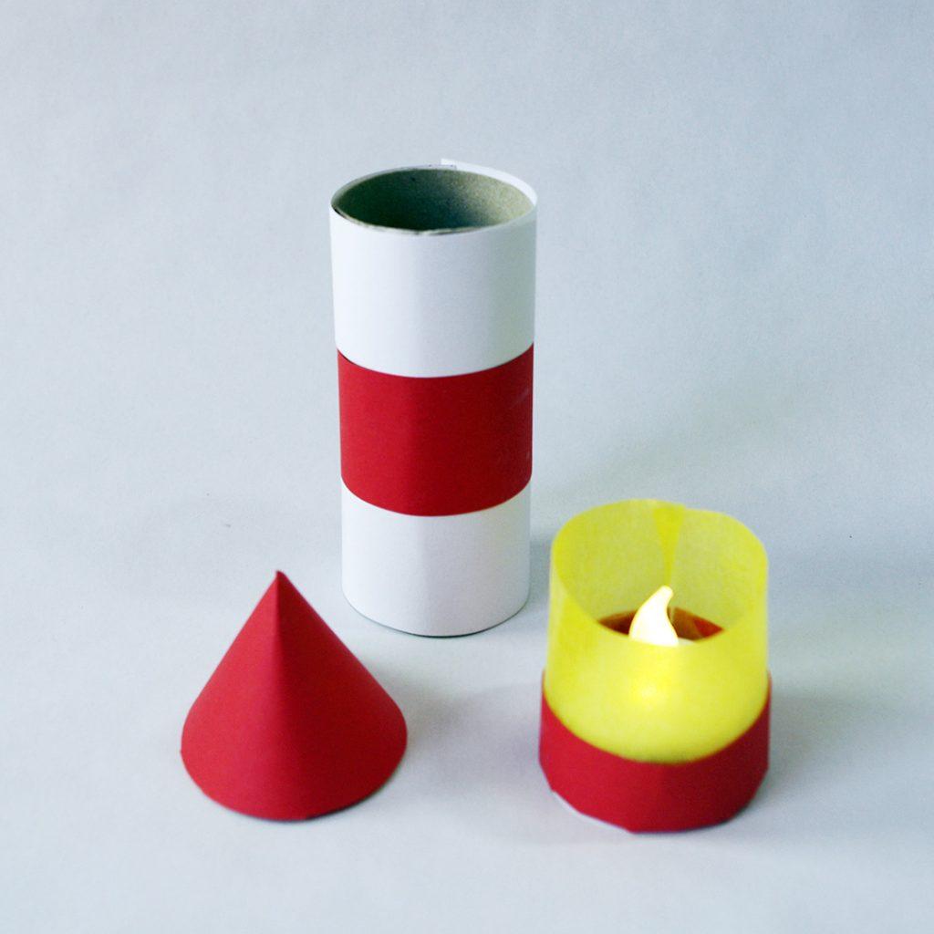 Fertige Einzelteile für den Leuchtturm. Mit Streifen beklebte Klopapierrolle, rotes, spitzes Dach und Teelicht im Ständer aus rotem Papier und gelbem Transparentpapier.