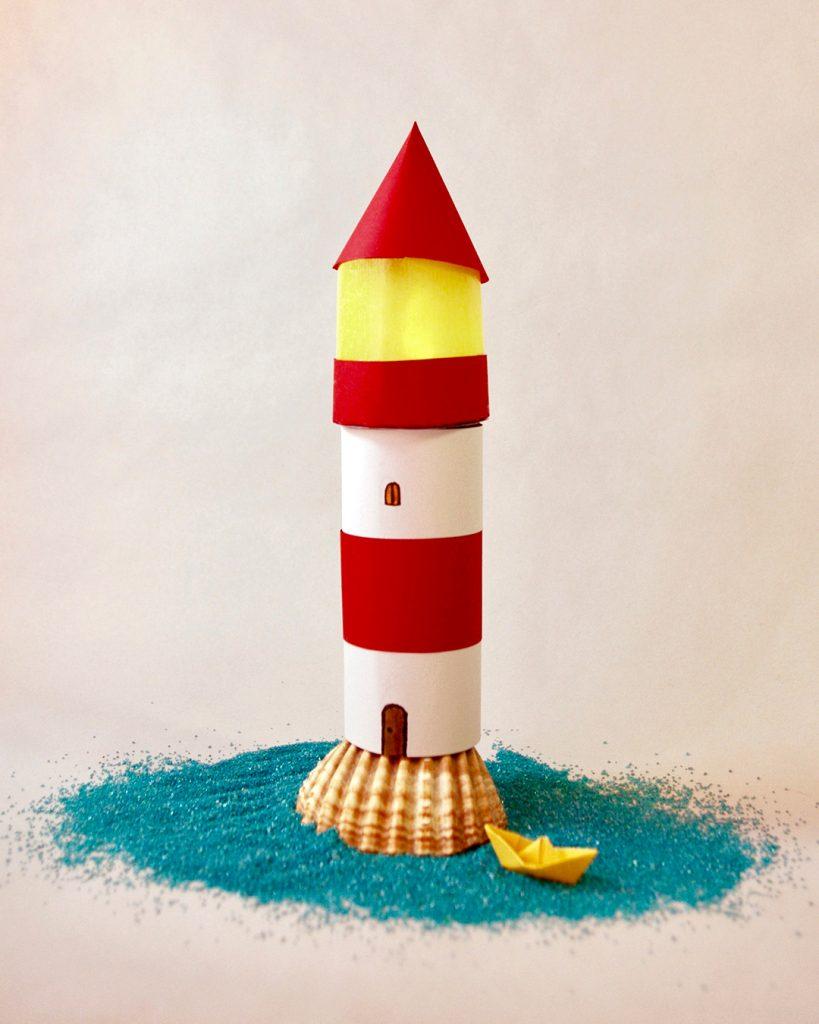 Ein selbstgebastelter Papp-Leuchtturm auf einem Muschelhügel in einem Meer aus blauen Sandkörnern. Am Rande ein gelbes Papierboot.