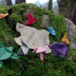 Kleine Origamis sitzen auf einem moosbedeckten Stein vor einer Miniatur-Schatzkarte.