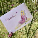 Eine Einladungskarte mit einer Zeichnung einer sitzenden Fee steckt zwischen blühenden Disteln.